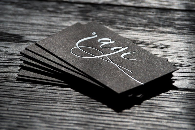 A stack of business cards designed by a creative agency in Kelowna