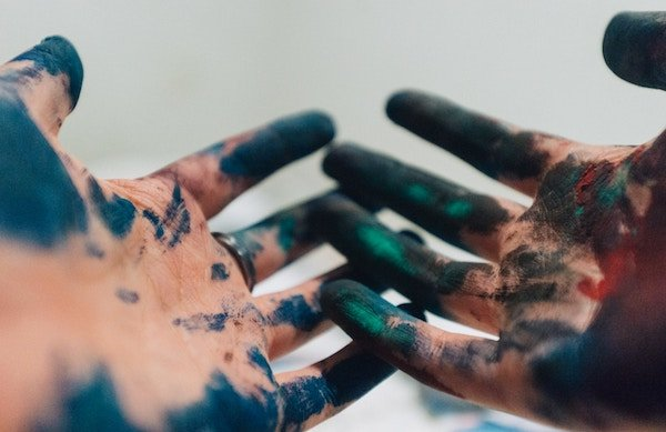 A pair of hands covered in paint reaching out