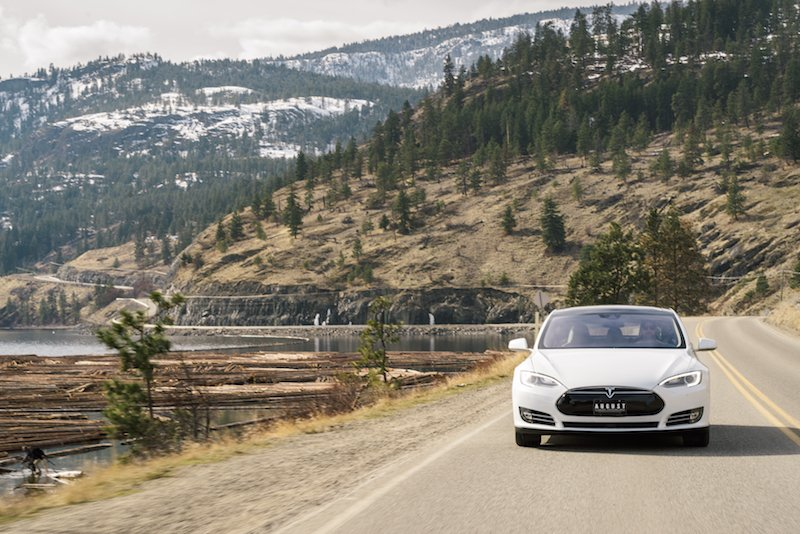 A Tesla car captured on a Sony Mirrorless camera driving around a lake in the Okanagan