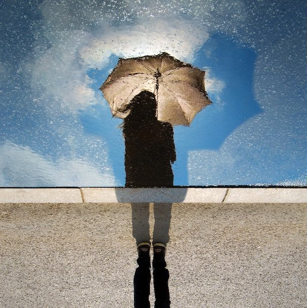 web design marketing seo | A female looking at the reflection of her umbrella, considering how it could help in design
