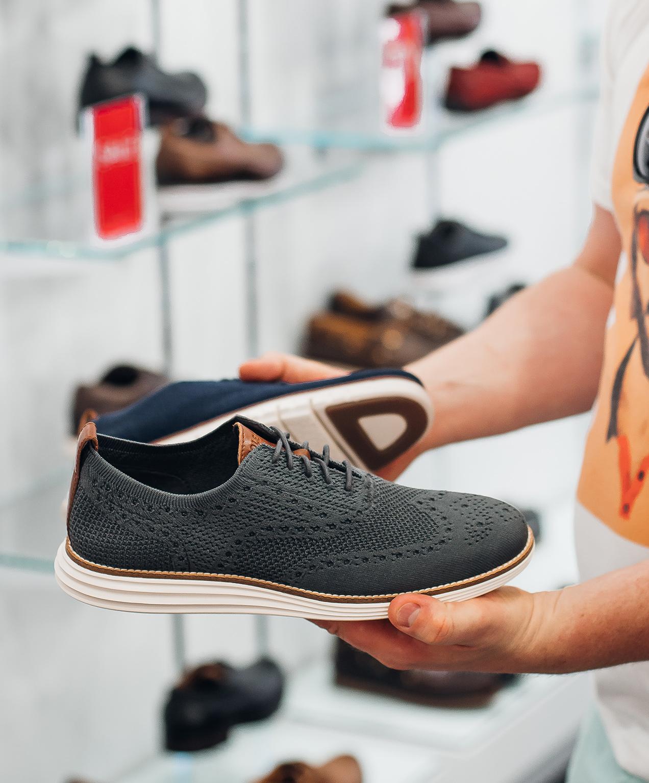 retail shoe store marketing employee holding shoes